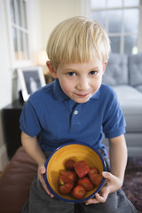 Portrait of boy with a bowl of strawberries..
