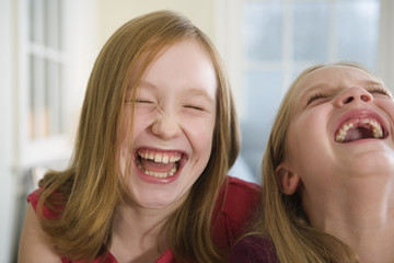 Close up of two sisters laughing.
