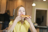 View of a girl eating a pizza..
