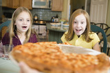 View of two girls looking at pizza.