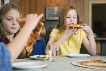 View of two girls eating pizza.