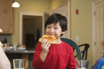 Portrait of a boy eating pizza..