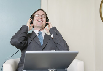View of a business man with laptop and headphones.