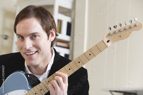 Portrait of a man holding guitar.
