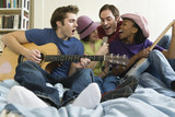 Two men and two women playing guitars in the bedroom.