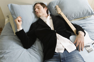Man sleeping in bed with guitar.