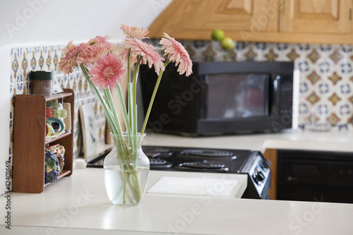 A flower vase with pink daisies in a kitchen.