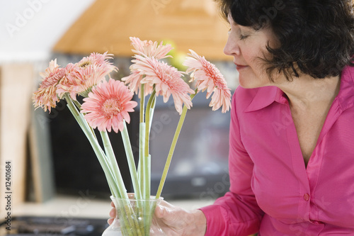 A woman smelling pink daisies.