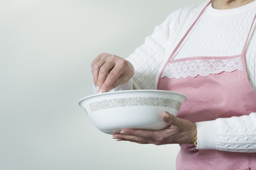 Midsection of a mature woman standing with a bowl.