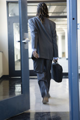 A young man walking through a doorway.