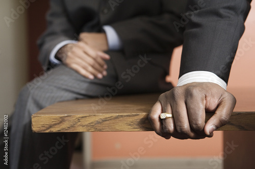 Close up of a businessman sitting on wooden desk.