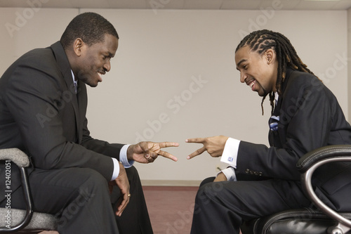 "Businessmen playin ""Rock Paper Scissors ""."