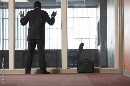 A Business man looking through a glass wall in an office.