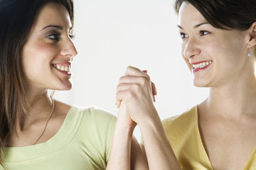Close up of two friends smiling and holding hands.