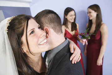 View of a cheerful bride hugging groom.