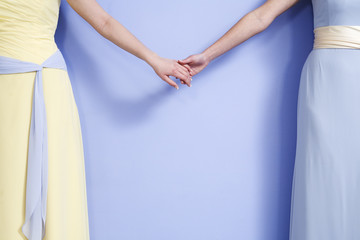 Midsection of two bridesmaids holding hands.