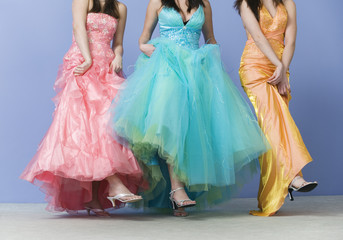 View of friends dancing wearing prom dresses.