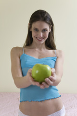 A beautiful young woman holding a green apple.
