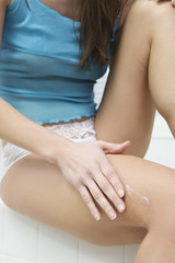A young woman applying cream on her body.