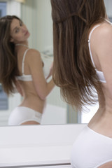 Young woman looking in a mirror.