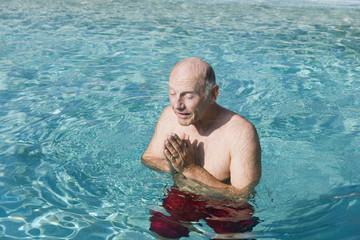 Senior man meditating in a swimming pool