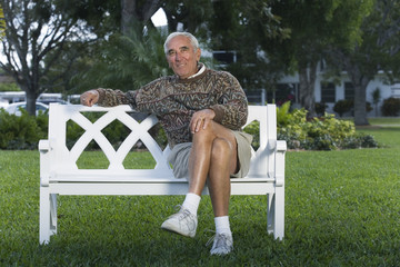 Portrait of a senior man sitting on a bench in a park.