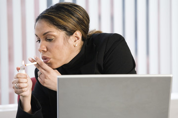 View of a business woman smoking in the office.