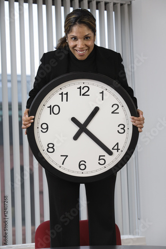 Portrait of a business woman holding wall clock.