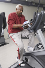 senior man exercising on stationary bike