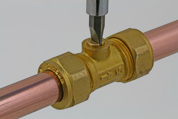 close up turning off service valve with screwdriver