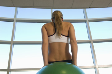 Woman Using Exercise Ball in Gym