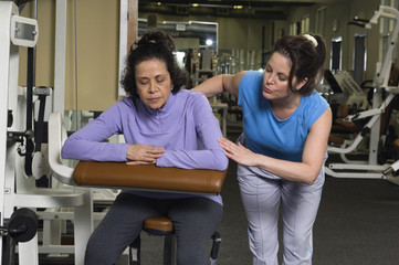 Trainer Assisting Senior Woman on Exercise Machine