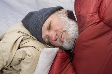 Senior man sleeping in a tent