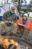 Senior couple eating by tent