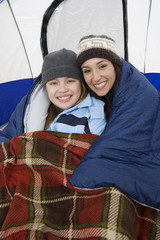 Mother and daughter embracing in tent, portrait