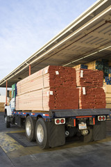 Truck loaded with wood outside warehouse
