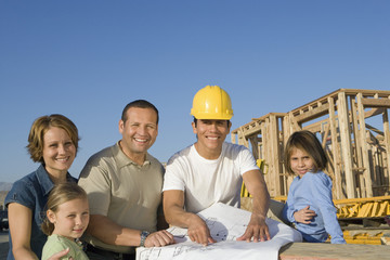 Portrait of family with two children 6-9 and construction side manager