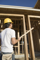 Construction worker carrying wooden beam