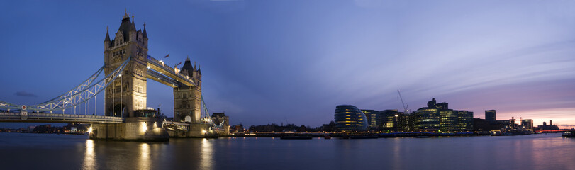 Panoramic evening time shot of Tower Bridge and city of London.