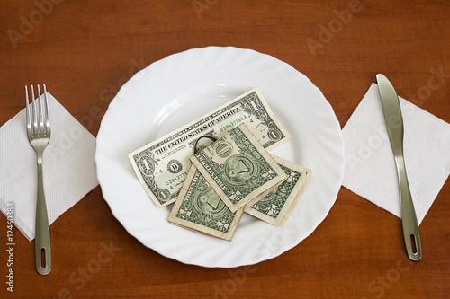 banknotes on a plate with knife and fork over wooden background