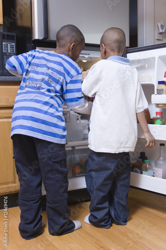 Two young boys looking in the refrigerator