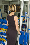 girl in health club doing exercise with gym apparatus poster