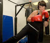 Attractive mature woman practicing kickboxing.