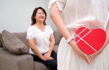 Hiding gift behind back, suprising mum
