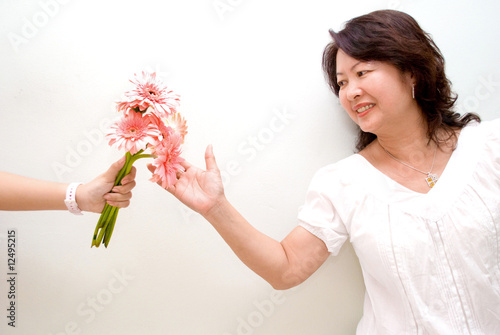 Asian lady reaching out for pink gerbera