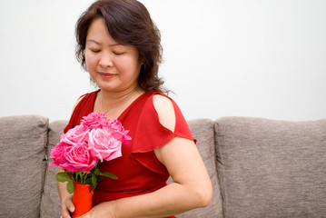 Asian lady looking at roses