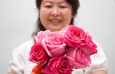 Close up shot of red pink roses with asian lady