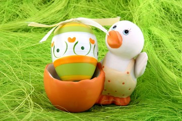 small duck and easter egg on green background