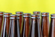 Empty beer bottles in diagonal rows in front of bright green