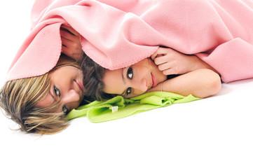 young girls under blanket smile